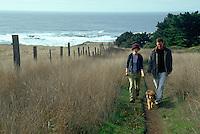 Young couple walking dog on coastal trail near Mendocino California