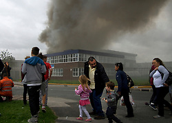 © Licensed to London News Pictures. 01/09/2013. Leyland, UK Children walk past the scene. The scene at Leyland St Mary's Catholic Technology College in Leyland, Lancashire as it was devastated by the blaze at 4pm yesterday (1st September 2013), which saw 100ft flames - and was tackled by 125 firefighters and 20 engines. Photo credit : Pat Tack/LNP