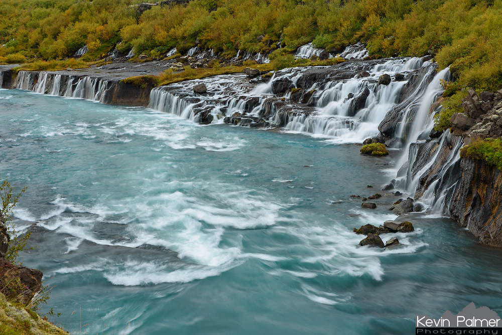 Iceland has no shortage of scenic waterfalls. This one is called Hraunfossar (meaning Lava Falls) and it's located near Húsafell in the western interior. The water splits into numerous cascades as it trickles through the mossy lava field and flows into the Hvítá River. Volcanic activity still heats the many hot springs found in this valley, which includes the most powerful one in Europe. The river is fed by the Langjökull Glacier, the 2nd largest in Iceland. Glacial silt suspended in the water gives it the beautiful turquoise color. A forest of short but colorful birch trees grew around the river, an unusual sight in this mostly treeless country.