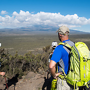 Hikers in the heath zone on Mt Kilimanjaro's Lemosho Trail with the peak of the mountain far in the distance partly obscured by clouds.