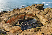 Devils Punchbowl was naturally carved by Pacific Ocean waves crashing into a rock headland, creating two caves which collapsed to leave two natural arches. Devils Punchbowl State Natural Area, Otter Rock, Oregon coast, USA.