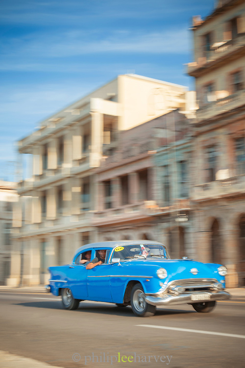 Vintage car driving along Malecon road between defocused buildings, Havana, Cuba