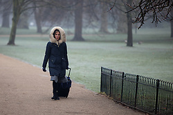 © Licensed to London News Pictures. 23/01/2017. London, UK. A woman wraps up in a large coat in St James's Park, as thick fog has covered London this morning, whilst temperatures drop to -2 degrees celsius. Photo credit : Tom Nicholson/LNP