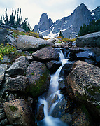 Small creek tumbling over boulders in the Cirque of the Towers, Warbonnet and Warrior peaks beyond, Wind River Range, Popo Agie Wilderness, Shoshone National Forest, Wyoming.