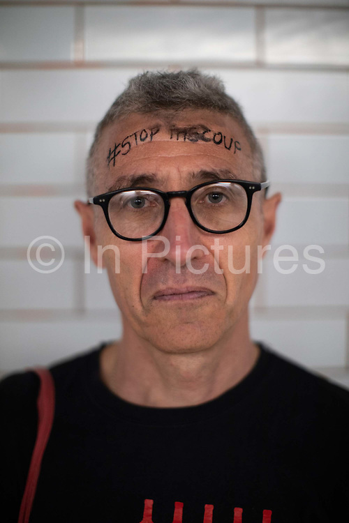 A male protester with Stop The Coup written, yet slightly smudged, on his forehead during the Stop The Coup protest against the proroguing of Parliament on 31st August 2019 in London in the United Kingdom. Left-wing group Momentum and the Peoples Assembly coordinated a series of Stop The Coup protests across the UK today, aimed at Boris Johnson and the UK government proroguing Parliament.