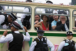 Environmental activists from Extinction Rebellion sit surrounded by Metropolitan Police officers on a vintage bus used by them to block a road junction to the south of London Bridge on the ninth day of their Impossible Rebellion protests on 31st August 2021 in London, United Kingdom. Extinction Rebellion are calling on the UK government to cease all new fossil fuel investment with immediate effect.