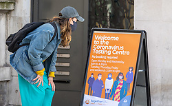 © Licensed to London News Pictures. 06/04/2021. London, UK. A member of the public looks at a sign outside a rapid Covid-19 test centre at Chelsea Town Hall, South West London as the government announce bi-weekly Covid tests from Friday for everyone in England. Photo credit: Alex Lentati/LNP