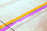Yellow and purple lane markers on an airport runway. WATERMARKS WILL NOT APPEAR ON PRINTS OR LICENSED IMAGES.
