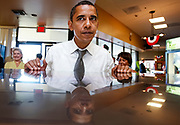 U.S. Democratic presidential nominee Senator Barack Obama (D-IL) is reflected in countertop as he places an order at a deli during a campaign stop in Ft. Lauderdale, Florida, October 21, 2008.   <br /> REUTERS/Jim Young