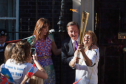 © licensed to London News Pictures. London, UK 26/07/2012. David Cameron posing with Florence Rowe who carry the torch out of Downing Street. Photo credit: Tolga Akmen/LNP