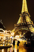 A couple carrying umbrellas stroll past bright lights and a carousel below the Eiffel Tower at night in Paris, France, while a homeless man slumps in the corner.