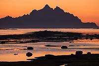 Vågakallen mountain peak rises above sea in morning twilight, Lofoten Islands, Norway