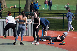 © Licensed to London News Pictures. 28/03/2020. London, UK. Members of the public exercising at Paddington Recreation Ground in London, during a lockdown over the spread of COVID-19. Prime Minister Boris Johnson has announced that people should only leave their homes for essential work, groceries, medical necessity and exercise. Photo credit: Ben Cawthra/LNP
