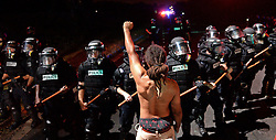 A protestor stands with his left arm and fist clenched as Charlotte-Mecklenburg police officers form a line on Old Concord Rd. on Tuesday night, Sept. 20, 2016 in Charlotte, N.C. The protest began on Old Concord Road at Bonnie Lane, where a Charlotte-Mecklenburg police officer fatally shot a man in the parking lot of The Village at College Downs apartment complex Tuesday afternoon. The man who died was identified late Tuesday as Keith Scott, 43, and the officer who fired the fatal shot was CMPD Officer Brentley Vinson. Photo by Jeff Siner/Charlotte Observer/TNS/ABACAPRESS.COM