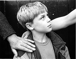 Young boy standing between man and woman with their hands on his shoulders,