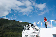 USA, Alaska,A woman enjoys the views from the back of a Alaska State Ferry on the Alaska Marine Highway system.