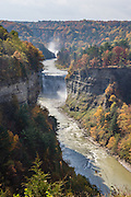 """From Inspiration Point, see Middle and Upper Genesee Falls amid the splendor of autumn leaf colors, at Letchworth State Park, near Portageville, New York, USA. In Letchworth State Park, renowned as the """"Grand Canyon of the East,"""" the Genesee River roars northeast through a gorge over three major waterfalls between cliffs as high as 550 feet, surrounded by diverse forests which turn bright fall colors in the last three weeks of October. The large park stretches 17 miles between Portageville and Mount Morris in the state of New York, USA. Drive or hike to many scenic viewpoints along the west side of the gorge. The best walk is along Gorge Trail #1 above Portage Canyon from Lower Genesee Falls (70 ft high), to Inspiration Point, to Middle Genesee Falls (tallest, 107 ft), to Upper Genesee Falls (70 ft high). High above Upper Falls is the railroad trestle of Portageville Bridge, built in 1875, to be replaced 2015-2016. Geologic history: in the Devonian Period (360 to 420 million years ago), sediments from the ancestral Appalachian mountains eroded into an ancient inland sea and became the bedrock (mostly shales with some layers of limestone and sandstone plus marine fossils) now exposed in the gorge. Genesee River Gorge is very young, as it was cut after the last continental glacier diverted the river only 10,000 years ago. The native Seneca people were largely forced out after the American Revolutionary War, as they had been allies of the defeated British. Letchworth's huge campground has 270 generously-spaced electric sites."""