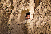 A young woman's hands stick out of a small window opening in the wall of a house near the Rock Palace near Sanaa, Yemen.