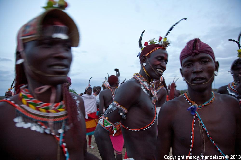 Samburu moran (warriors) in a celebratory mood following their graduation ceremony into senior warrior status.  Outside Kisima village, Samburu, Kenya.  August 22, 2013.