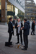 Young men after work drink outside a bar at Monument, their beers on the pavement, on 9th December 2016, in the City of London.