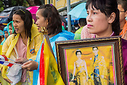"05 MAY 2013 - BANGKOK, THAILAND:  A Thai woman holds an old picture of Bhumibol Adulyadej, the King of Thailand, and his wife Queen Sirikit Sunday while she waits to see them. The King and Queen, who are both hospitalized and in poor health, did not attend Sunday's event. May 5 marks the 63rd anniversary of the Coronation of His Majesty King Bhumibol Adulyadej. The day is celebrated as a national holiday; since this year it falls on a Sunday, it will be observed on Monday May 6, and as such all government offices and commercial banks will close for the day. HM King Bhumibol Adulyadej is the longest reigning monarch in the world. Each year on the 5th of May, the Kingdom of Thailand commemorates the day when, in 1950, the Coronation Ceremony was held for His Majesty King Bhumibol Adulyadej, the 9th in the Chakri Dynasty (Rama IX). On the 5th of May, His Majesty conducts a merit making ceremony, presenting offerings to Buddhist monks, and leads a ""Wien Thien"" ceremony, walking three times around sacred grounds at the Temple of the Emerald Buddha.    PHOTO BY JACK KURTZ"