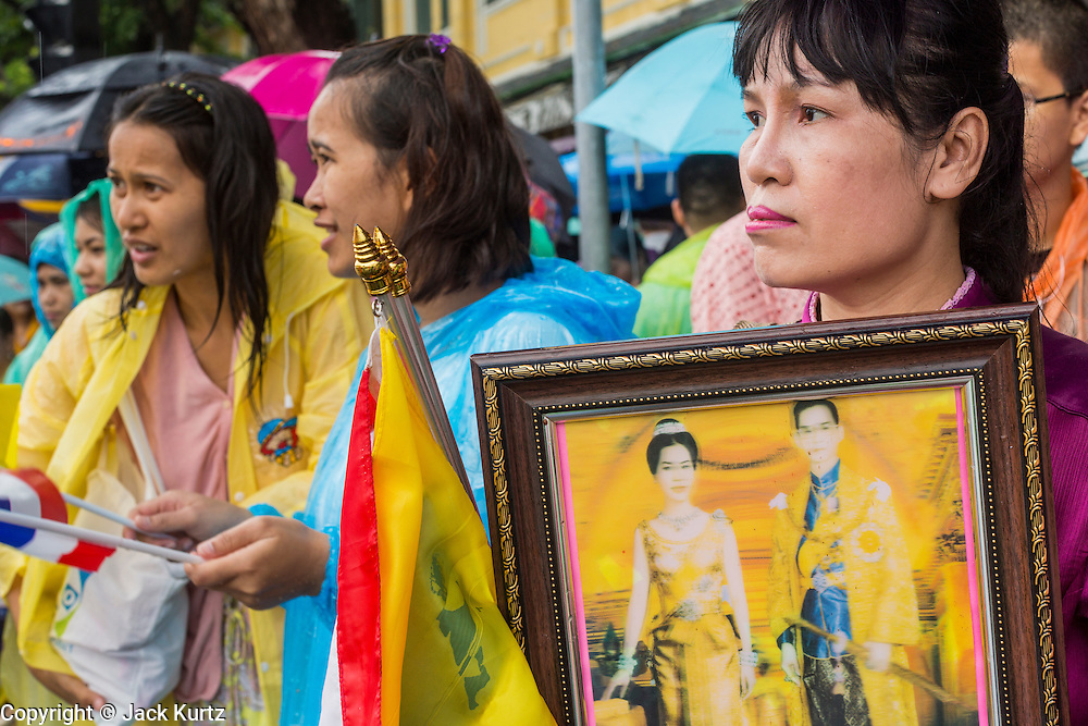 """05 MAY 2013 - BANGKOK, THAILAND:  A Thai woman holds an old picture of Bhumibol Adulyadej, the King of Thailand, and his wife Queen Sirikit Sunday while she waits to see them. The King and Queen, who are both hospitalized and in poor health, did not attend Sunday's event. May 5 marks the 63rd anniversary of the Coronation of His Majesty King Bhumibol Adulyadej. The day is celebrated as a national holiday; since this year it falls on a Sunday, it will be observed on Monday May 6, and as such all government offices and commercial banks will close for the day. HM King Bhumibol Adulyadej is the longest reigning monarch in the world. Each year on the 5th of May, the Kingdom of Thailand commemorates the day when, in 1950, the Coronation Ceremony was held for His Majesty King Bhumibol Adulyadej, the 9th in the Chakri Dynasty (Rama IX). On the 5th of May, His Majesty conducts a merit making ceremony, presenting offerings to Buddhist monks, and leads a """"Wien Thien"""" ceremony, walking three times around sacred grounds at the Temple of the Emerald Buddha.    PHOTO BY JACK KURTZ"""