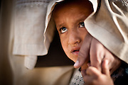 An Afghan child looks out from under his father's cloak as American and Afghan soldiers interrogate his father.