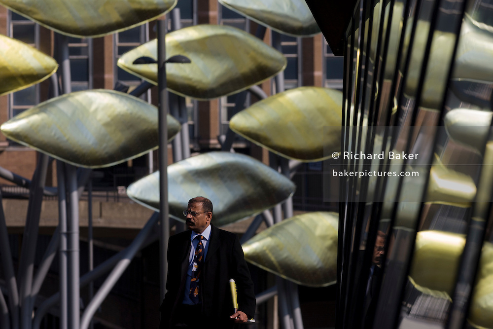 Businessman of south Asian descent on walkway with the new Olympic kinetic artwork called the Shoal at Stratford. 'The Shoal' at the Stratford Centre, east London, is made up of around 100 titanium clad 'leaves' mounted between 15 and 19 metres high on metal posts. Worth £13.5m, the Shoal is part of The Stratford Town Centre Public Realm Project, designed and manufacturered using 3D technology.