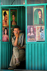 KABUL,AFGHANISTAN - SEPT. 12:  An Afghan sits inside a music store next to posters of famous Indian Bollywood stars in Kabul, Afghanistan September 12,2002. Since the fall of the Taliban, Indian  movies and music have flooded the Afghan market and is hugely popular but the Ministry of Culture has recently banned showing Indian movies on television because it is considered too risque by some.   (Photo by Ami Vitale/Getty Images)