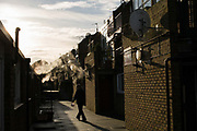A man silhouetted by the setting sun at Cressingham Gardens Estate on 9th January 2015 in South London, United Kingdom. Cressingham Gardens is a council garden estate, located on the southern edge of Brockwell Park. It comprises of 306 dwellings and built to the design of Lambeth Borough Council architect Edward Hollamby in the early 1970s. In 2012, Lambeth Council proposed regeneration of the estate, a decision highly opposed by many residents. Since the announcement, the highly motivated campaign group Save Cressingham Gardens has been active.