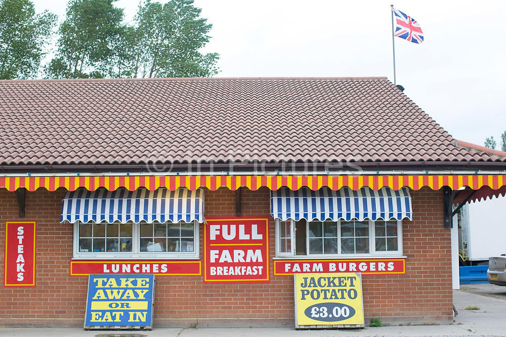 Bright and colourful breakfast and takeaway food signs at the Farm Cafe in rural Holbeach on the 23rd June 2017 in Norfolk, United Kingdom. Established during the 1950's after the owners parents set up a tea stop on the east bound A17, the cafe has grown over the years and attracts coach loads of tourist and travellers often en route to the north Norfolk coast.