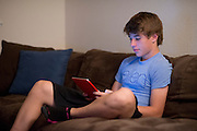 Alex Lee aka #AlexFromTarget plays with his new iPad he received from Ellen DeGeneres at his home on November 10, 2014 in Frisco, Texas. (Cooper Neill for The New York Times)