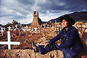 Taos Pueblo, New Mexico, USA. A man on the adobe wall of the cemetery.