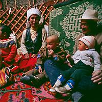 """Nomadic Kyrgyz family inside felt """"akoi"""" (yurt) near Lake Karakol."""
