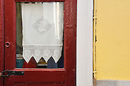 Red door with white crochet curtain in Syros, Greece
