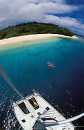 Two snorkellers explore the clear waters off a tropical island, from thier charter yacht. Vava'u islands, Tonga