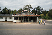 PANOLA, AL – OCTOBER 9, 2015: Students from North Sumter Junior High School walk in front of the former Bank's General Store off of Highway 34. Due to state budget cuts, Alabama announced the closure of 31 of its driver's license offices in mostly rural sections of the state, where poverty is high and transportation is notoriously difficult. Critics argue the closures are an attempt to limit accessibility to photo IDs – which are now required for voting – but state officials insist that the closings have no effect on access to photo ID. CREDIT: Bob Miller for The New York Times