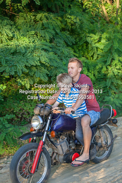 Boy riding on a Polish teens motorcycle traveling over a graveled country road age 18 and 10. Zawady Central Poland