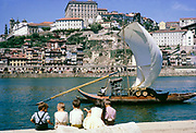 A series of images about port wine production in Portugal c 1960 - traditional rabelo boat with oak barrels in city of Porto, children sitting on quayside