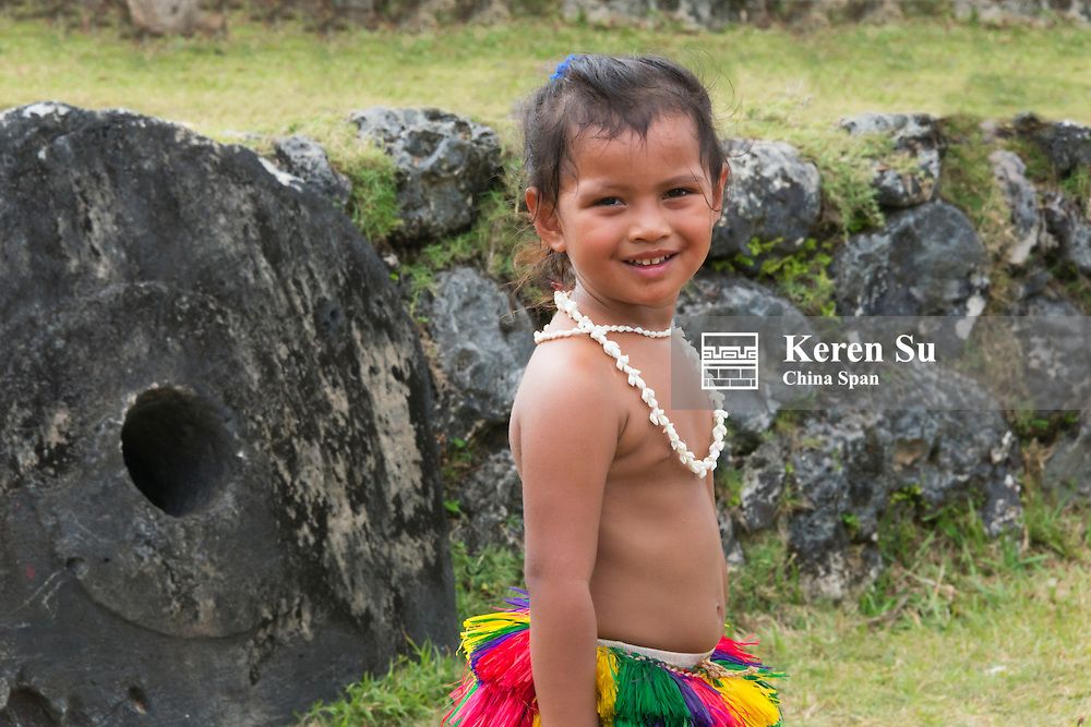 Little Yapese girl in traditional clothing with stone money at Yap Day Festival, Yap Island, Federated States of Micronesia