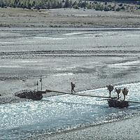 Trekkers and porters cross the Kali Gandaki River near Jomsom, Nepal.