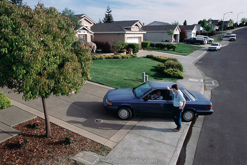 Usa.mw2.700.xs..Craig Caven talks to a neighbor coming home from work, in the driveway of his American Canyon, California, home. {{Craig Caven, 38, and Regan Ronayne, 42, and their two children, Andrea, 5, and Ryan 3, live in a multi-cultural bedroom community called American Canyon, California, about one hour north of San Francisco.}}.