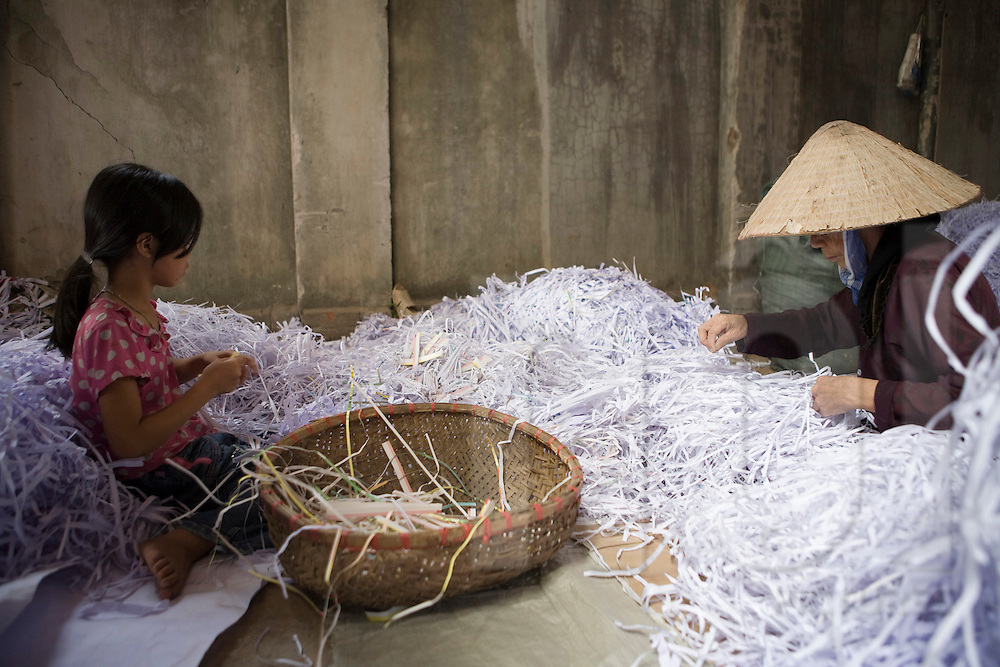 Workshop of recycling paper in the village of Cham Khe close from Hanoi. A child and mother recycling paper