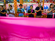 "29 MARCH 2017 - BANG KRUAI, NONTHABURI, THAILAND: A sheet is pulled just before people about to go through their ritualistic death during a ""Resurrection Ceremony"" stand in their coffins at Wat Ta Kien (also spelled Wat Tahkian), a Buddhist temple in the suburbs of Bangkok. People go to the temple to participate in a ""Resurrection Ceremony."" Groups of people meet and pray with the temple's Buddhist monks. Then they lie in coffins, the monks pull a pink sheet over them, symbolizing their ritualistic death. The sheet is then pulled back, and people sit up in the coffin, symbolizing their ritualist rebirth. The ceremony is supposed to expunge bad karma and bad luck from a person's life and also get people used to the idea of the inevitability of death. Most times, one person lays in one coffin, but there is family sized coffin that can accommodate up to six people. The temple has been doing the resurrection ceremonies for about nine years.          PHOTO BY JACK KURTZ"