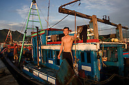 A fisherman brings his boat into dock at the fishing harbor in Nha Trang. The boats off load their catch, which is take to local and out-of-town markets. Robert Dodge, a Washington DC photographer and writer, has been working on his Vietnam 40 Years Later project since 2005. The project has taken him throughout Vietnam, including Hanoi, Ho Chi Minh City (Saigon), Nha Trang, Mue Nie, Phan Thiet, the Mekong, Sapa, Ninh Binh and the Perfume Pagoda. His images capture scenes and people from women in conical hats planting rice along the Red River in the north to men and women working in the floating markets on the Mekong River and its tributaries. Robert's project also captures the traditions of ancient Asia in the rural markets, Buddhist Monasteries and the celebrations around Tet, the Lunar New Year. Also to be found are images of the emerging modern Vietnam, such as young people eating and drinking and embracing the fashions and music of the West. His book. Vietnam 40 Years Later, was published March 2014 by Damiani Editore of Italy.