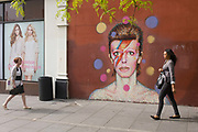 Young women walk past the mural of iconic musician and singer David Bowie has appeared on the wall of Morleys department store in Brixton, Lambeth, south London. The Bowie face is sourced (by an unknown artist) from the cover of his 1973 album Aladdin Sane at the height of his 1970s fame. The pop icon lived at 40 Stansfield Road, Brixton, from his birth in 1947 until 1953. This cover appeared in Rolling Stone's list of the 500 greatest albums of all time, making #277.