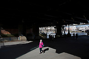 Woman passes from shadow to sunlight while walking under Hungerford Bridge. The South Bank is a significant arts and entertainment district, and home to an endless list of activities for Londoners, visitors and tourists alike.