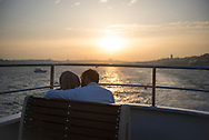 Istanbul, Turkey - November 8, 2017: A couple aboard a ferry crosses the Bosphorus Strait at sunset in Istanbul, Turkey