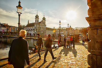 People take a late afternoon stroll along the Reuss River in the town of Lucerne in central Switzerland