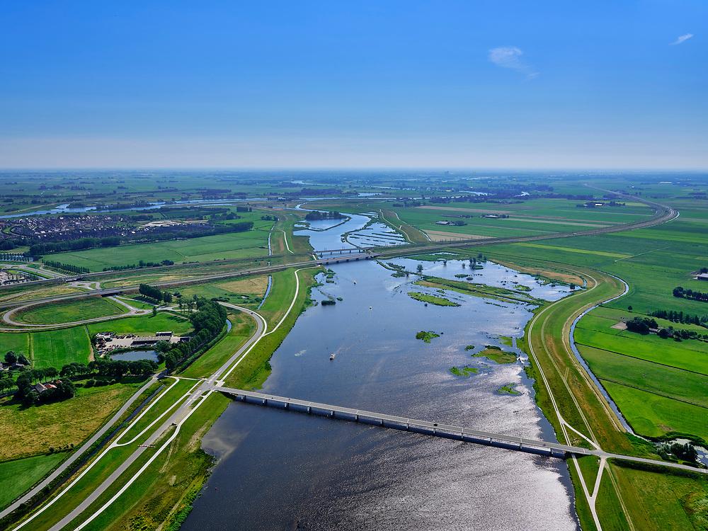 """Nederland, Overijssel, Gemeente Kampen; 21–06-2020; het Reevediep richting IJssel met  Nieuwendijkbrug in de voorgrond en gezien naar Reevediepbrug(rijksweg N50) en spoorbrug Reevediep. Voor de ze bruggen natuurgebied De Enk.<br /> Het Reevediep is aangelegd in het kader van het project Ruimte voor de Rivier om bij hoogwater water af te voeren voordat dit het nabij gelegen Kampen bereikt, direct naar het IJsselmeer, de 'bypass Kampen'. Het Reevediepgebied is ook een natuurgebied en vormt een ecologische verbindingszone tussen rivier de IJssel en Drontermeer.<br /> Reevediep in the direction of river IJssel, seen from the new Nieuwendijk bridge.<br /> The Reevediep has been constructed as part of the Room for the River project, and functions to discharge high waters before reaching the nearby Kampen, directly to the IJsselmeer, the """"bypass Kampen"""". The Reevediep area is also a nature reserve and forms an ecological connecting zone between the river IJssel and Drontermeer.<br /> <br /> luchtfoto (toeslag op standaard tarieven);<br /> aerial photo (additional fee required)<br /> copyright © 2020 foto/photo Siebe Swart"""